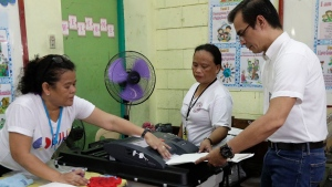 """Manila mayor candidate Francisco """"Isko"""" Moreno Domagoso, right, is helped by election workers as he casts his vote at the Manuel L. Quezon elementary school in Manila, Philippines, Monday, May 13, 2019. (AP Photo/Aaron Favila)"""