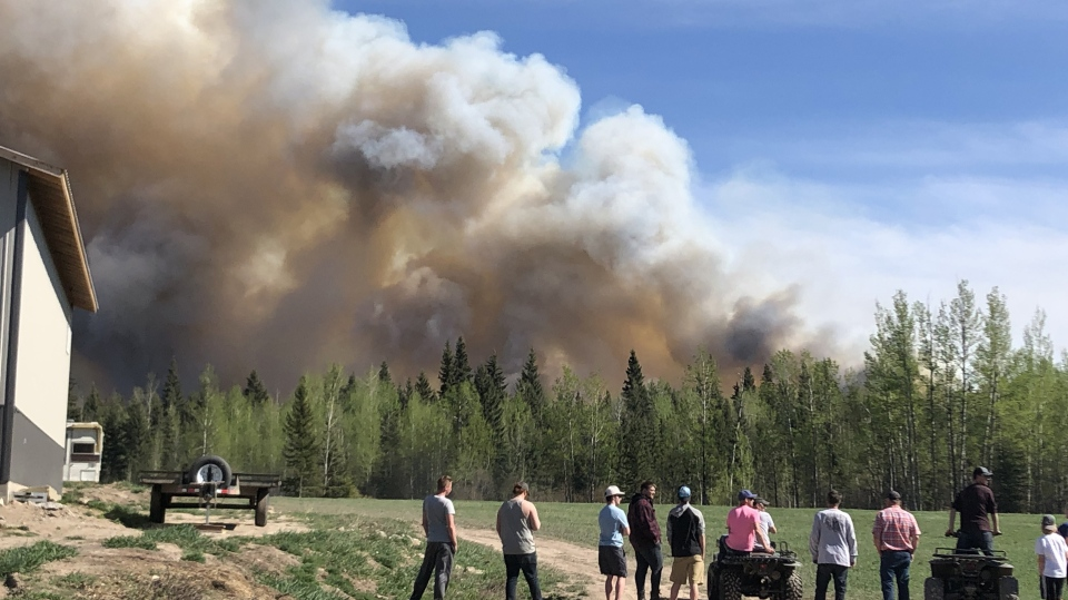People watch a wildfire burn in Fraser Lake, B.C., Saturday, May 11, 2019. An active wildfire in central British Columbia has prompted a local state of emergency and several evacuations. (THE CANADIAN PRESS/HO)