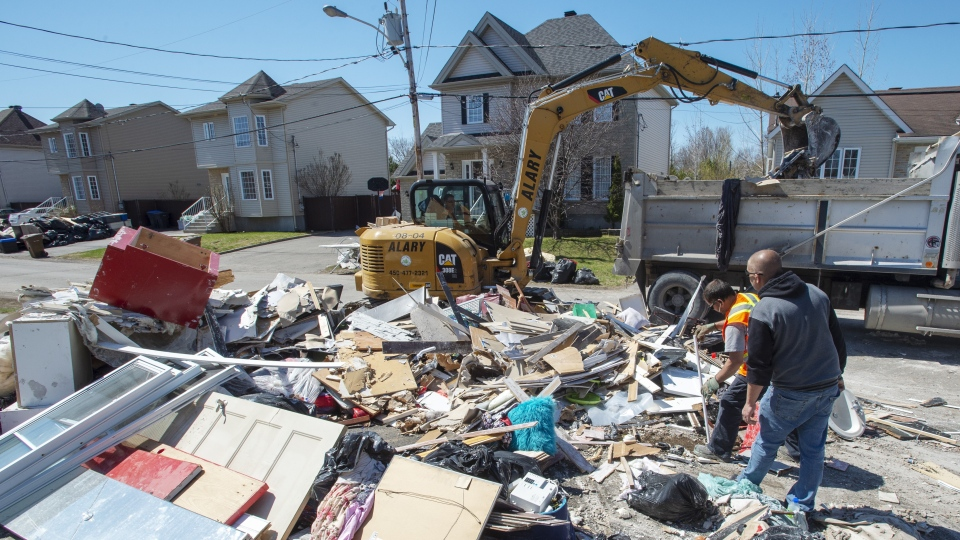 Workers clean up debris as clean up continues in certain sectors of in Ste-Marthe-sur-la-Lac, Que., Monday, May 6, 2019. (THE CANADIAN PRESS/Ryan Remiorz)