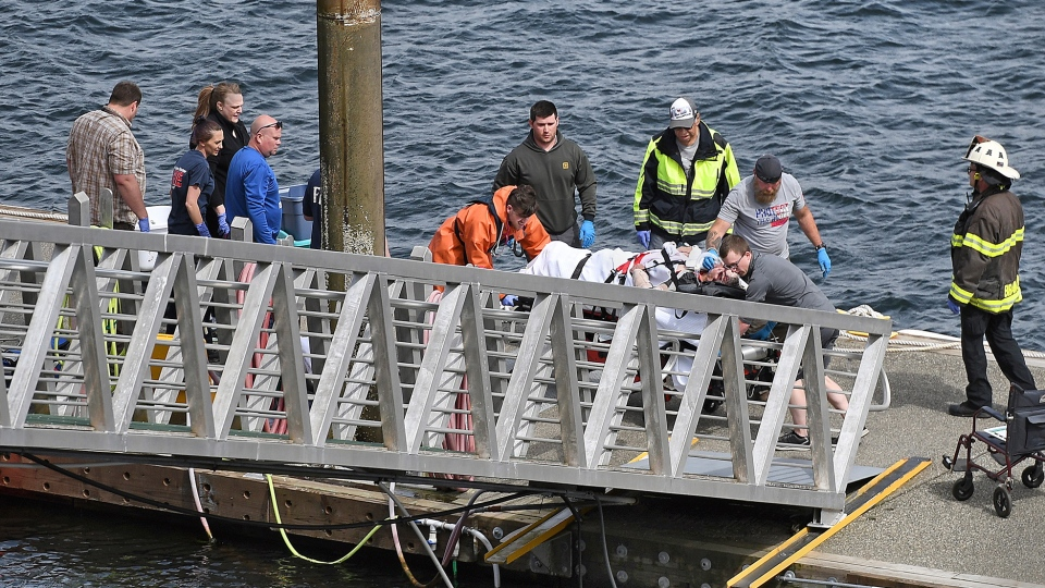 Emergency response crews transport an injured passenger to an ambulance at the George Inlet Lodge docks, Monday, May 13, 2019, in Ketchikan, Alaska. (Dustin Safranek/Ketchikan Daily News via AP)