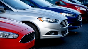 FILE- In this Nov. 19, 2015, photo, a row of new Ford Fusions are for sale on the lot at Butler County Ford in Butler, Pa. (AP Photo/Keith Srakocic, File)