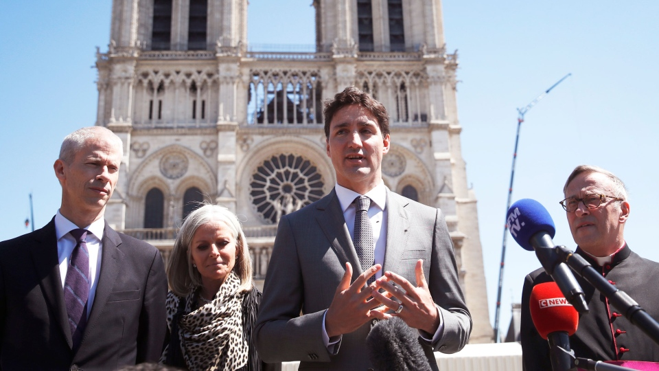 Prime Minister Justin Trudeau, center, addresses reporters after visiting Notre Dame cathedral with Notre Dame Cathedral rector Patrick Chauvet, right, Canadian Ambassador to France Isabelle Hudon, second left, and French Culture Minister Franck Rieste, in Paris, Wednesday, May 15, 2019. (AP Photo/Christophe Ena)