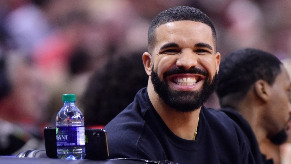 Drake smiles as he sits court at the Toronto Raptors versus Orlando Magic NBA action and watches the Toronto Maple Leafs NHL game on his phone during first half NBA basketball playoff action in Toronto on Tuesday, April 23, 2019. (THE CANADIAN PRESS/Frank Gunn)