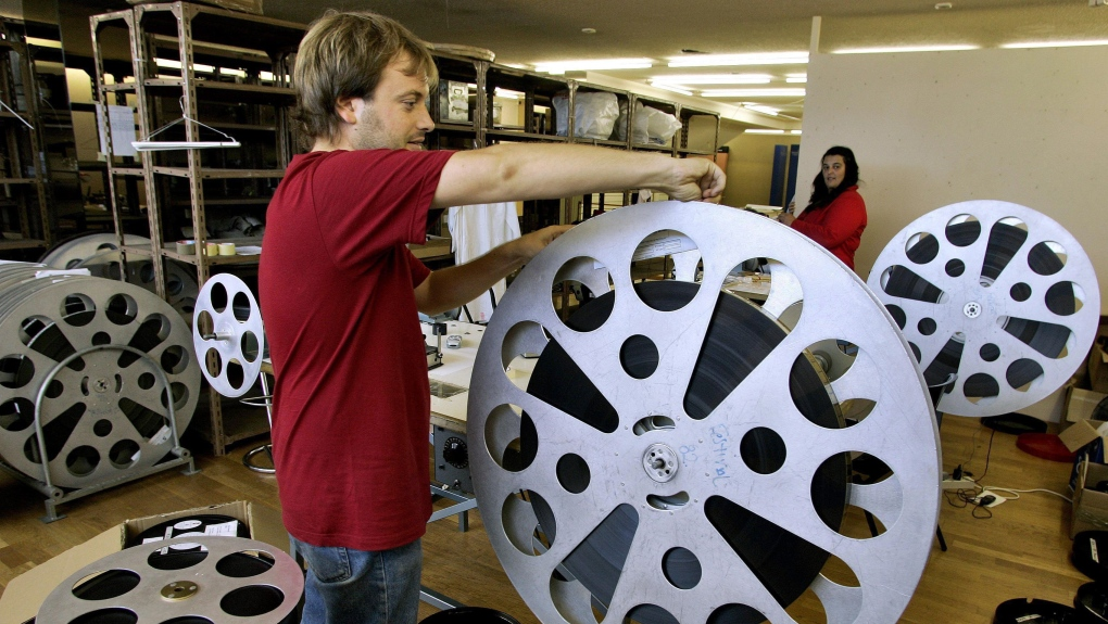 A worker prepares a movie reel