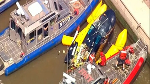 In this image made from video provided by WABC-TV, harbor units from the New York City police and fire departments work to secure a helicopter to the dock after it crashed in the Hudson River, Wednesday, May 15, 2019 in New York. (WABC-TV via AP)