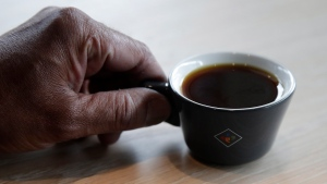Klatch Coffee owner Bo Thiara holds a cup of Elida Natural Geisha coffee at his shop in San Francisco, Wednesday, May 15, 2019.  (AP Photo/Jeff Chiu)