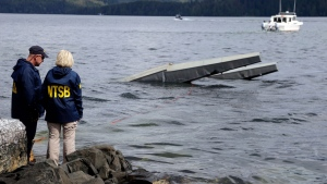 In this photo provided by the National Transportation Safety Board, NTSB investigator Clint Crookshanks, left, and member Jennifer Homendy stand near the site of some of the wreckage of the DHC-2 Beaver, Wednesday, May 15, 2019, that was involved in a midair collision near Ketchikan, Alaska, a couple of days earlier. (Peter Knudson / NTSB via AP)