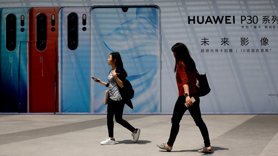 Chinese women walk by the new Huawei P30 smartphone advertisement on display outside a shopping mall in Beijing, Thursday, May 16, 2019.(AP Photo/Andy Wong)