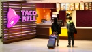 In this April 19, 2019, file photo, travelers look at a menu at a Taco Bell restaurant inside Miami International Airport in Miami. (AP Photo/Wilfredo Lee, File)