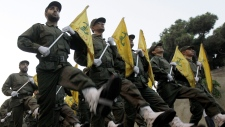 Hezbollah fighters parade in a suburb of Beirut