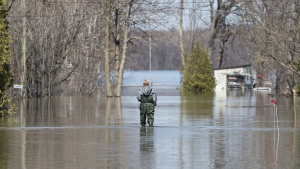 A woman wades through floodwaters on a residential street in the town of Rigaud, Que, west of Montreal, Monday, April 22, 2019. THE CANADIAN PRESS/Graham Hughes