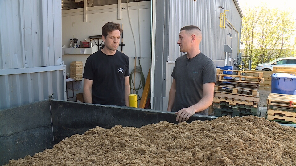 Joe van Heerden with District Brewing Co. (L) and area farmer Colton Fink (R) preparing to send off a bin of spent grain. (Gareth Dillistone/CTV Regina)