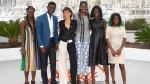 Actors Aminata Kane, from left, Amadou Mbow, director Mati Diop, actors Mame Sane, Nicole Sougou, and Mariama Gassama pose for photographers at the photo call for the film 'Atlantique' at the 72nd international film festival, Cannes, southern France, Friday, May 17, 2019. (Photo by Arthur Mola/Invision/AP)