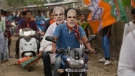 In this April 2, 2019 file photo, Bharatiya Janata Party (BJP) supporters wear masks of Indian Prime Minister Narendra Modi and ride a motorbike during an election campaign rally ahead of general elections in Borhola village, Assam state, India. (AP Photo/Anupam Nath, File)