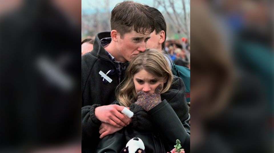 In this April 25, 1999 file photo, shooting victim Austin Eubanks hugs his girlfriend during a community wide memorial for the victims of the shooting rampage at Columbine High School. Eubanks, who survived the 1999 Columbine school shooting and later became an advocate for fighting addiction has died. (AP Photo/Bebeto Matthews, File)