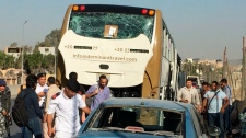 Police inspect a car and a bus that were damaged by a bomb, in Cairo, Egypt, Sunday, March 19, 2019. Egyptian officials say a roadside bomb has hit a tourist bus near the Giza Pyramids. (AP Photo/Mohammed Salah)