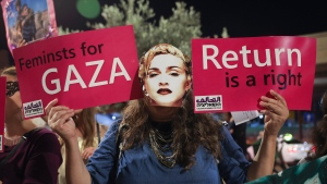 A supporter of Coalition of Women for Peace wears a mask depicting Madonna during a protest for lifting the Gaza blockade and to boycott the 2019 Eurovision Song Contest, outside the venue where the contest final will take place, in Tel Aviv, Israel, Saturday, May 18, 2019. (AP Photo/Oded Balilty)