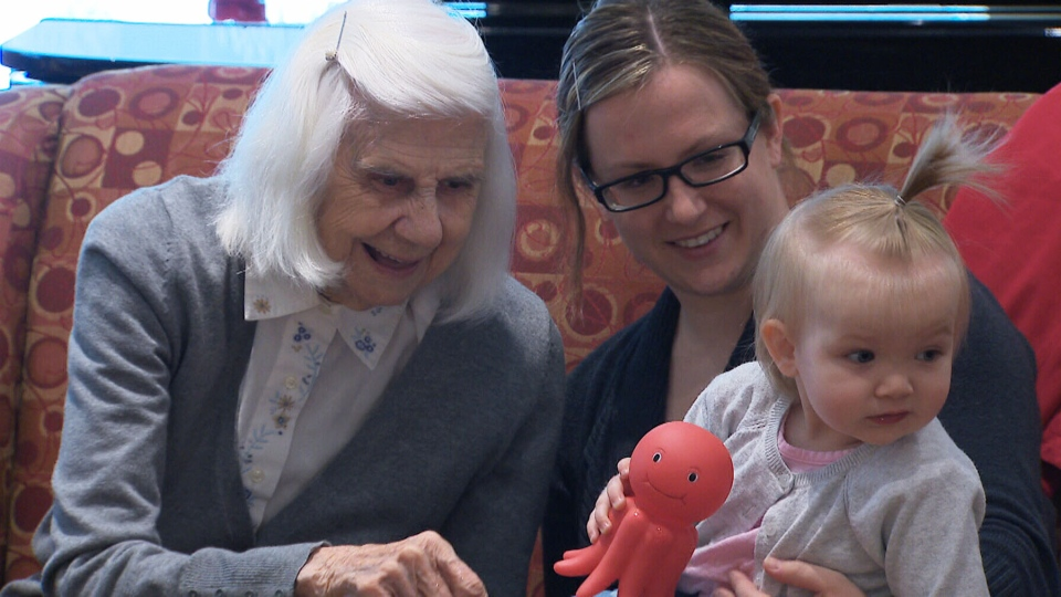 An Ottawa senior plays with a volunteer baby during a 'Babies who volunteer' visit.