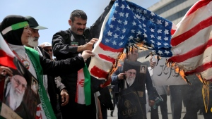 Iranian worshippers burn a representation of a U.S. flag during a rally after Friday prayer in Tehran, Iran, Friday, May 10, 2019. (AP Photo/Ebrahim Noroozi)