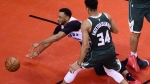 Toronto Raptors forward Norman Powell (24) draws a foul going to the net as Milwaukee Bucks forward Giannis Antetokounmpo (34) looks on during the second half of Game 3 NBA Eastern Conference finals basketball action in Toronto on Sunday, May 19, 2019. THE CANADIAN PRESS/Frank Gunn