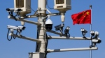 A Chinese national flag flutters near the surveillance cameras mounted on a lamp post in Tiananmen Square in Beijing, Friday, March 15, 2019. (AP Photo/Andy Wong)