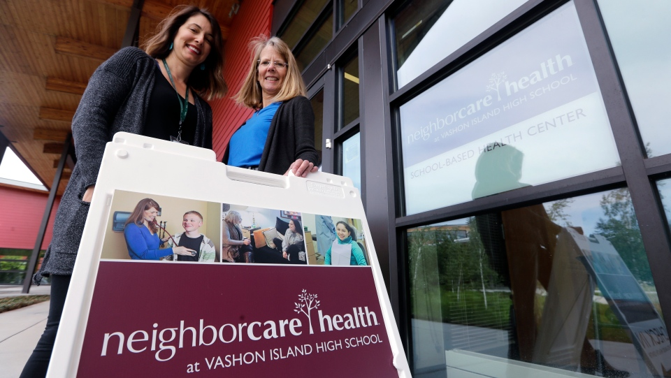 In this photo taken Wednesday, May 15, 2019, Neighborcare Health clinic manager Stephanie Keller, left, stands with Vashon Island High School nurse Sarah Day at the school campus clinic, where top service provided at the student-based health center is vaccinations, in Vashon Island, Wash. (AP Photo/Elaine Thompson)