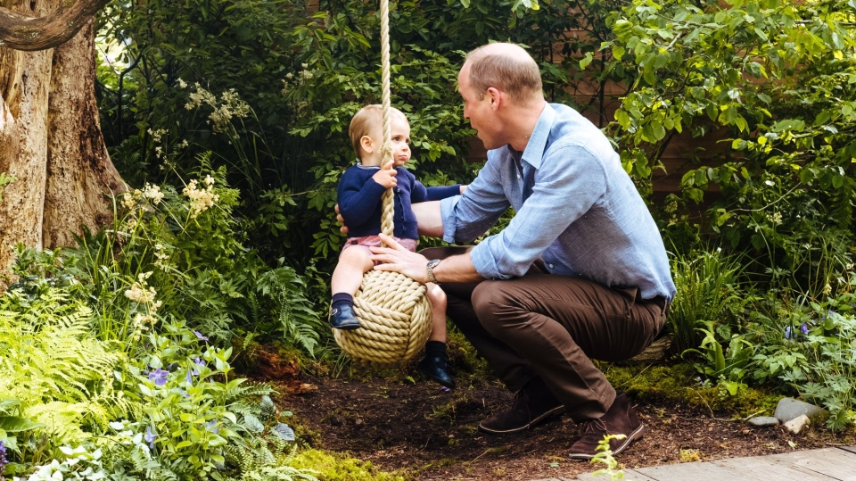 Prince Louis, who turned one in April, was pictured practicing his walk through the garden and enjoying a ride on the rope swing with the help of his father. (Matt Porteous)
