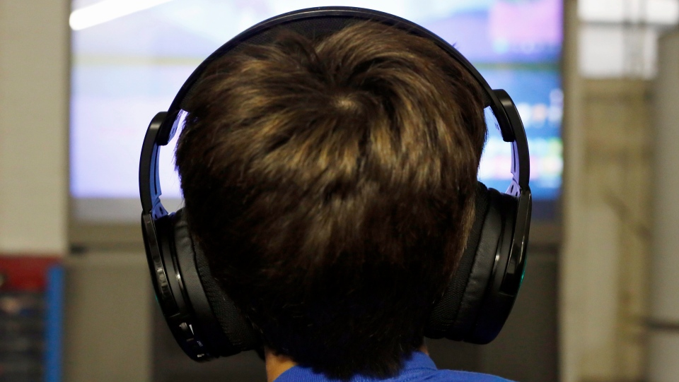 "FILE- In this Oct. 6, 2018, file photo Henry Hailey, 10, plays one of the online ""Fortnite"" game in the early morning hours in the basement of his Chicago home. (AP Photo/Martha Irvine, File)"