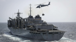 "In this Sunday, May 19, 2019, photo released by the U.S. Navy, an MH-60S Sea Hawk helicopter from the ""Nightdippers"" of Helicopter Sea Combat Squadron 5 transports cargo from the fast combat support ship USNS Arctic to the Nimitz-class aircraft carrier USS Abraham Lincoln during a replenishment-at-sea in the Arabian Sea.(Mass Communication Specialist 3rd Class Jeff Sherman/U.S. Navy via AP)"