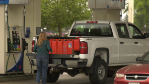 A Canadian woman fills several jerrycans full of cheap U.S. fuel before coming back over the border.