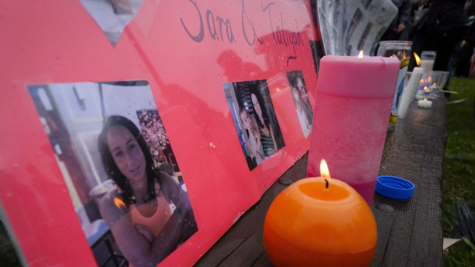 Lit candles and photographs are seen on display at a vigil for Calgary homicide victims Sara Baillie and her five-year-old daughter Taliyah Marsman, in Calgary, on July 17, 2016. (THE CANADIAN PRESS/Jeff McIntosh)