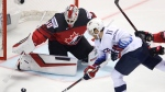 Canada's goaltender Matt Murray, left, makes a save against Luke Kunin of the U.S., right, during the Ice Hockey World Championships group A match between Canada and the United States at the Steel Arena in Kosice, Slovakia, Tuesday, May 21, 2019. (AP Photo/Petr David Josek)