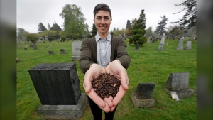 FILE - In this April 19, 2019, file photo, Katrina Spade, the founder and CEO of Recompose, a company that hopes to use composting as an alternative to burying or cremating human remains, poses for a photo in a cemetery in Seattle, as she displays a sample of compost material left from the decomposition of a cow using a combination of wood chips, alfalfa and straw.   (AP Photo/Elaine Thompson, File)