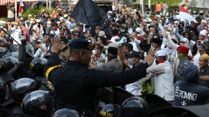 Indonesian police officers block supporters of Indonesian presidential candidate Prabowo Subianto during a rally outside the Elections Supervisory Agency (Bawaslu) building in Jakarta, Indonesia, Tuesday, May 21, 2019. (AP Photo/Achmad Ibrahim)