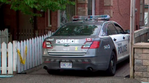 A Toronto police cruiser sits in the driveway of a Dovercourt Park where officers say a man was found dead on May 22, 2019.