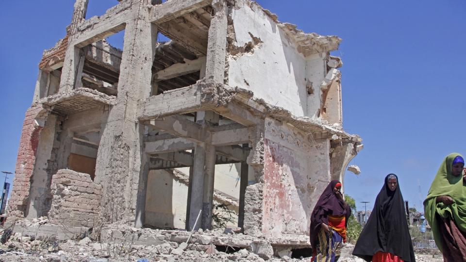 Somali women walk past a destroyed building after a suicide car bomb attack in the capital Mogadishu, Somalia, on May 22, 2019. (Farah Abdi Warsameh / AP)