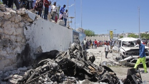 Somalis look at the wreckage after a suicide car bomb attack in the capital Mogadishu, Somalia, on May 22, 2019. (Farah Abdi Warsameh / AP)