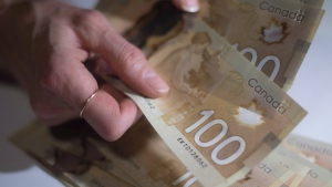 Canadian $100 bills are counted in Toronto, Feb. 2, 2016. (Graeme Roy / THE CANADIAN PRESS)