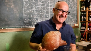 Prof. Aren Maeir, from Bar Ilan University, holds an ancient jar and a glass of beer during a press conference in Jerusalem, Wednesday, May 22, 2019. Israeli researchers celebrated Wednesday a long-brewing project of making beer and mead using yeasts extracted from ancient clay vessels -- some over 5,000 years old(AP Photo/Sebastian Scheiner)