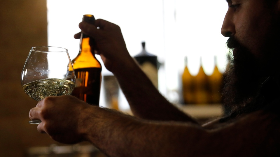 Craft brewer from Biratenu, the Jerusalem Beer Center, Shmuel Naky, right, pours beer during a press conference in Jerusalem, Wednesday, May 22, 2019. (AP Photo/Sebastian Scheiner)