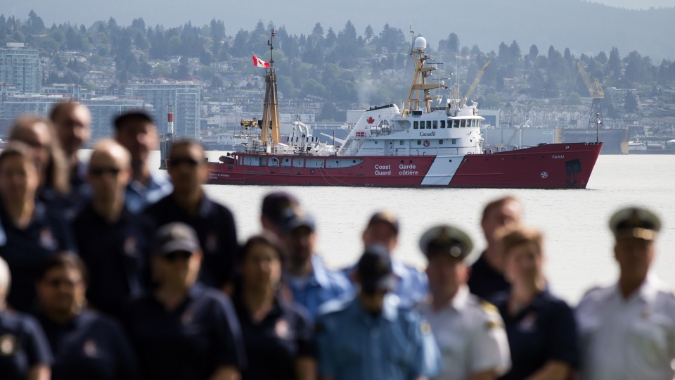 The Canadian Coast Guard fisheries patrol vessel Tanu is seen in the distance on the harbour as coast guard members listen to Prime Minister Justin Trudeau speak in Vancouver, on Wednesday May 22, 2019. THE CANADIAN PRESS/Darryl Dyck