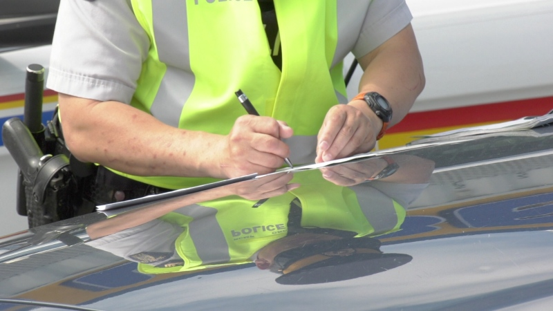 An RCMP officer writes a speeding ticket during a speed enforcement campaign in May.