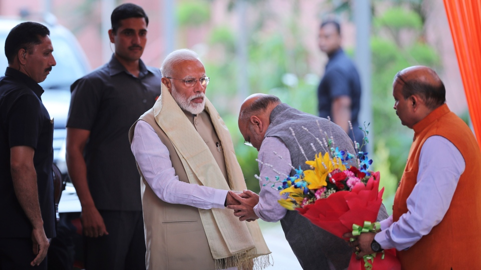 Bharatiya Janata Party (BJP) President Amit Shah, center, greets Indian Prime Minister Narendra Modi upon his arrival at the party headquarters for a function to thank cabinet members for their service in the term that is about to end, in New Delhi, India, Tuesday, May 21, 2019. (AP Photo/Manish Swarup)