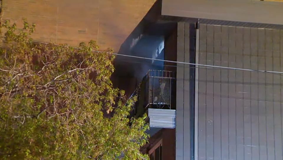 Emergency rews remain at the scene of a fire at an apartment building in the city's southwest.