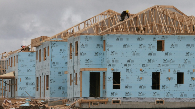 A construction worker works on a house in a new housing development in this file photo. (Richard Buchan / THE CANADIAN PRESS)