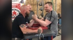 Two people seen arm wrestling.