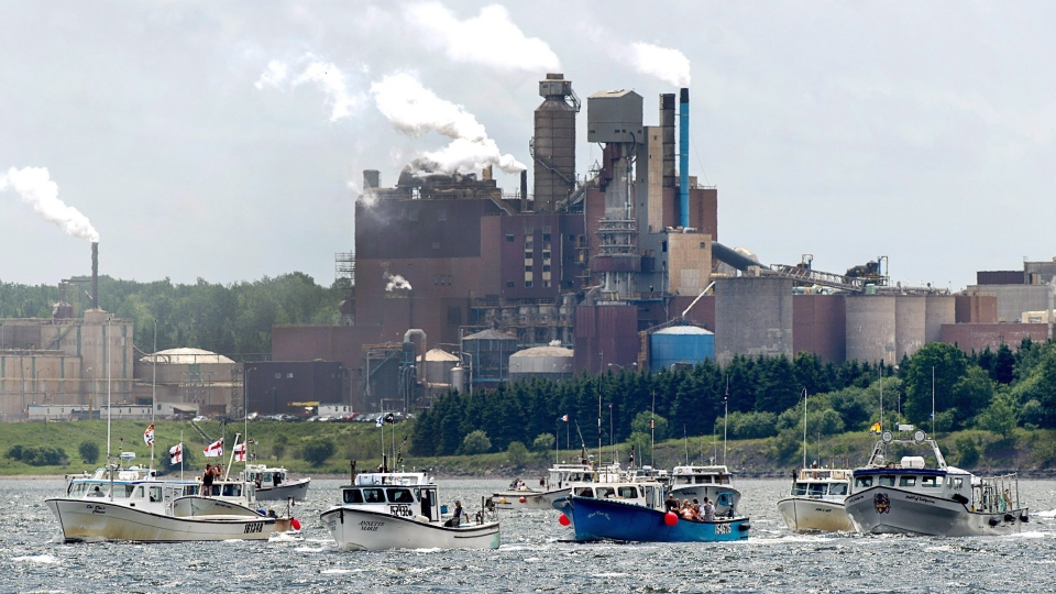 Fishing boats pass the Northern Pulp mill as concerned residents, fishermen and Indigenous groups protest the mill's plan to dump millions of litres of effluent daily into the Northumberland Strait in Pictou, N.S., on July 6, 2018.  (THE CANADIAN PRESS/Andrew Vaughan)