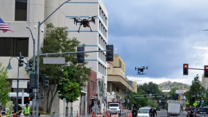 In this Tuesday, May 21, 2019 photo, two drones fly above Lake Street in downtown Reno, Nev., on, as part of a NASA simulation to test emerging technology that someday will be used to manage travel of hundreds of thousands of commercial, unmanned aerial vehicles (UAVs) delivering packages. (AP Photo/Scott Sonner)