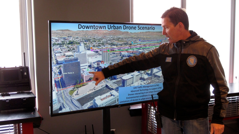 In this Tuesday, May 21, 2019 photo, Chris Walach, executive director of the Nevada Institute of Autonomous Systems, points to the the launch pad on a casino parking garage in downtown Reno, Nev., where NASA conducted the first drone tests of their kind in an urban setting. (AP Photo/Scott Sonner)