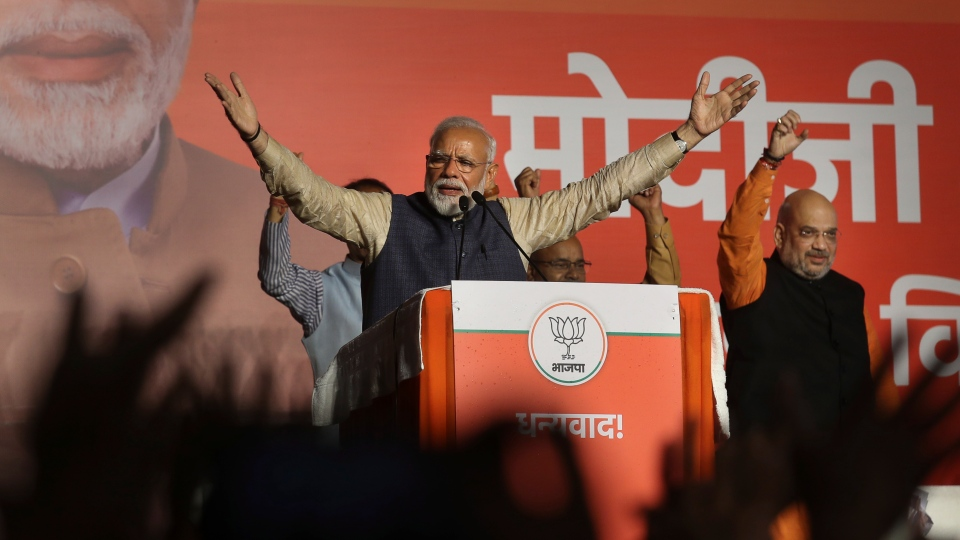 Indian Prime Minister Narendra Modi addresses party supporters, standing next to his Bharatiya Janata Party (BJP) President Amit Shah at their headquarters in New Delhi, India, Thursday, May 23, 2019. (AP Photo/Manish Swarup)